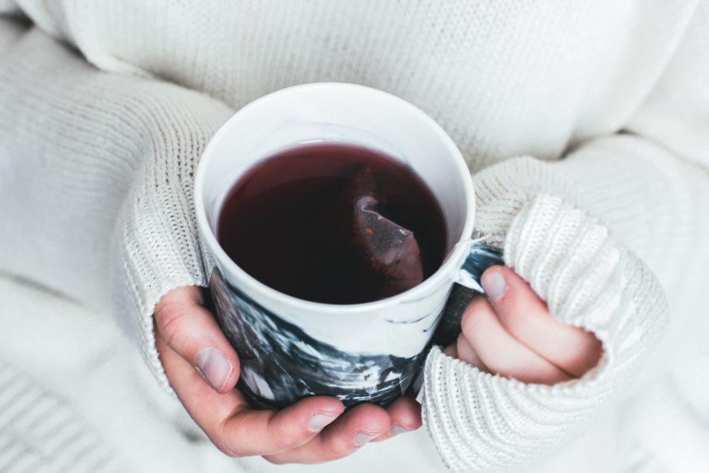 Händer som håller i en kopp med te