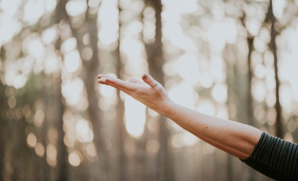 hand som sträcker sig mot himlen